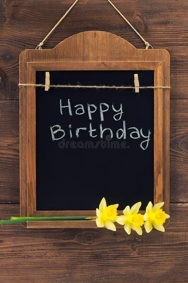 O feliz aniversario escrito com giz no quadro-negro envelhecido com narciso floresce a suspensão na parede de madeira fotos de stock royalty free