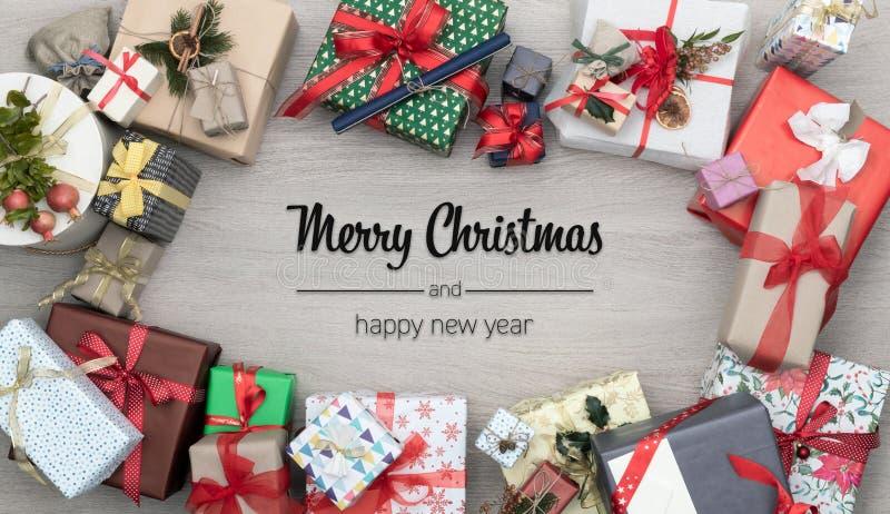 O Feliz Natal e os cumprimentos do ano novo feliz na tabela de madeira vertical da vista superior completamente de presentes do N fotografia de stock