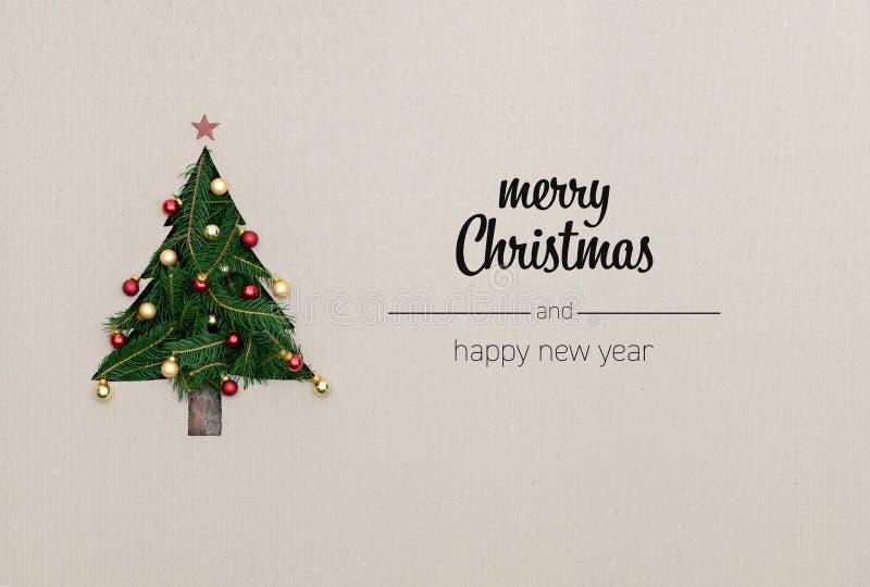 O Feliz Natal e os cumprimentos do ano novo feliz no cartão vertical da vista superior com eco natural decoraram a árvore de Nata fotografia de stock