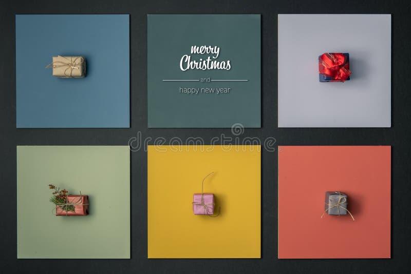 O Feliz Natal moderno e os cumprimentos do ano novo feliz em quadros coloridos verticais da vista superior com as caixas do prese foto de stock royalty free