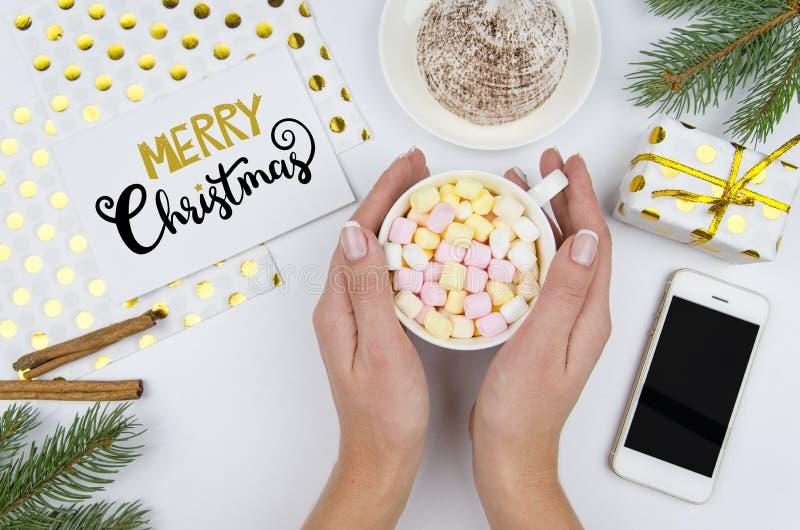 O Feliz Natal que rotula com abeto ramifica, decorações douradas Uma menina que guarda um copo com marshmallows Telefone em branc fotos de stock