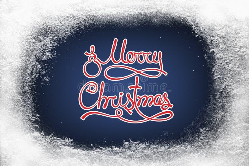 O Feliz Natal text na geada azul da neve do fundo e da geada na janela do xmas fotografia de stock