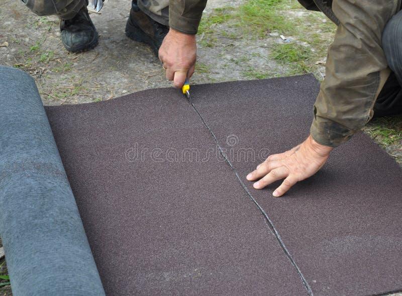O feltro ou o betume do telhado do rolo do corte do Roofer durante waterproofing trabalham imagem de stock royalty free