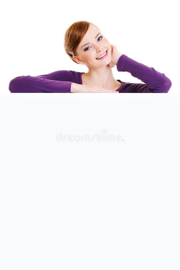 o femalel de sorriso está sobre uma placa da publicidade fotos de stock royalty free