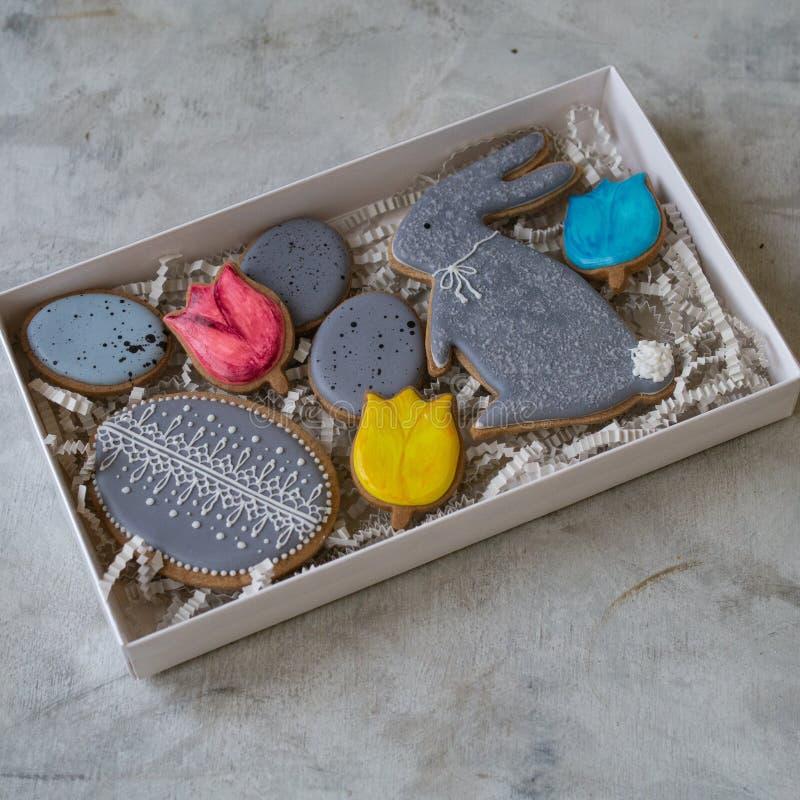 O feriado feliz da família, apresenta na caixa, nas cookies de easter do pão-de-espécie no formulário dos coelhos e nos ovos Cook fotos de stock royalty free