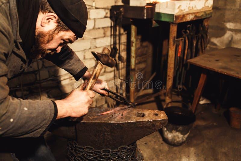 O ferreiro faz um forjamento artístico do metal quente no batente imagem de stock