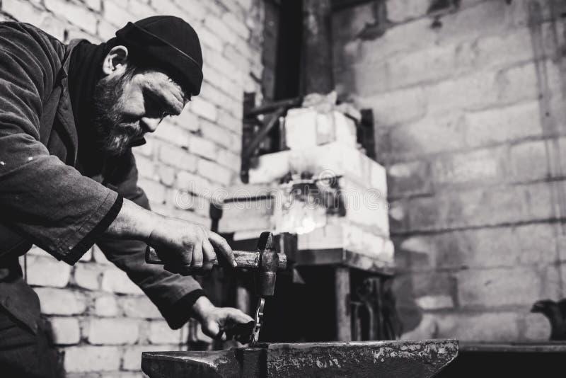 O ferreiro faz um forjamento artístico do metal quente no batente fotos de stock