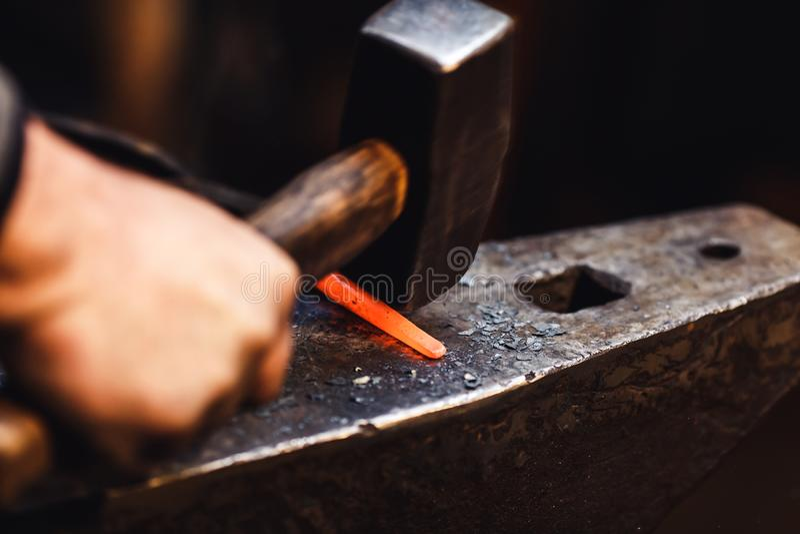 O ferreiro faz um forjamento artístico do metal quente no batente fotografia de stock royalty free