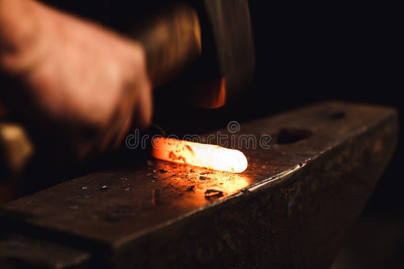 O ferreiro faz um forjamento artístico do metal quente no batente foto de stock