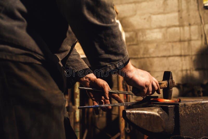 O ferreiro faz um forjamento artístico do metal quente no batente fotos de stock royalty free