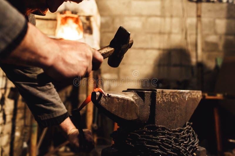 O ferreiro faz um forjamento artístico do metal quente no batente imagens de stock