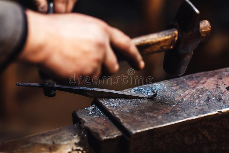 O ferreiro faz um forjamento artístico do metal quente no batente imagens de stock royalty free