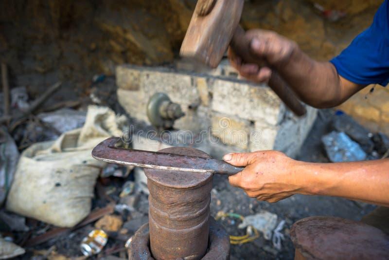 O ferreiro faz uma faca rural tradicional na província de Cao Bang, Vietname foto de stock royalty free