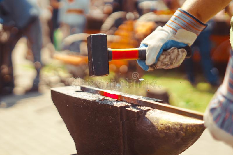 O ferreiro forja o ferro foto de stock