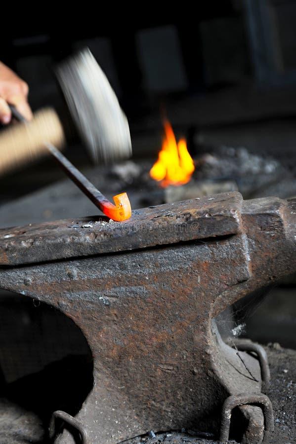 O ferreiro forja o ferro imagem de stock