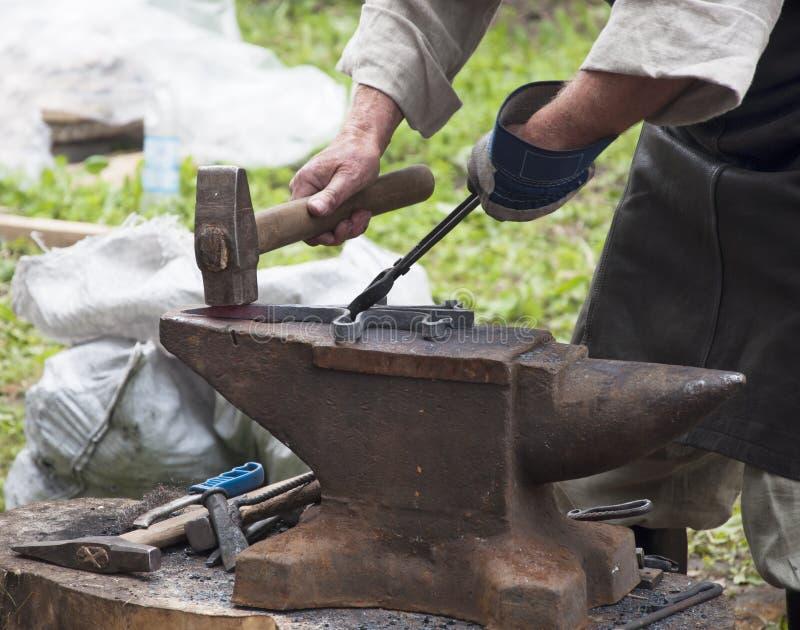 O ferreiro forja o ferro fotos de stock