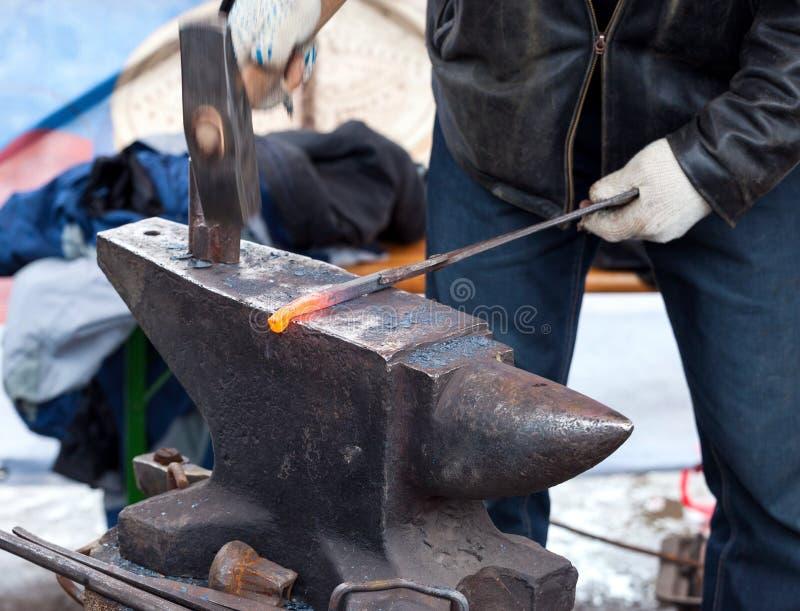 O ferreiro forja o ferro na forja fotos de stock