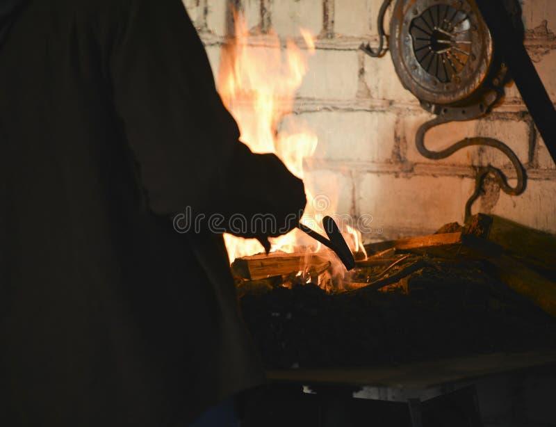 O ferreiro forja um ferro encarnado fotografia de stock