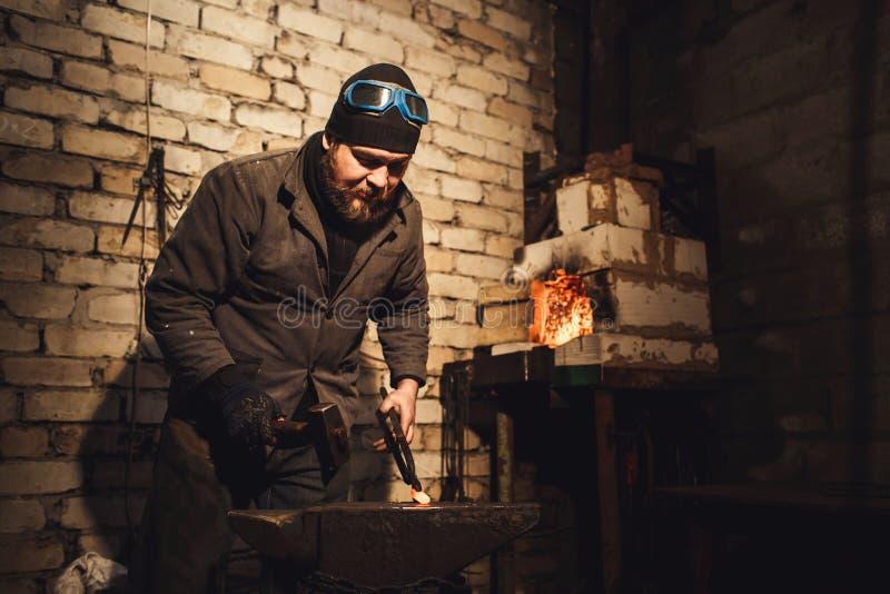 O ferreiro forja um metal quente no batente com um martelo foto de stock