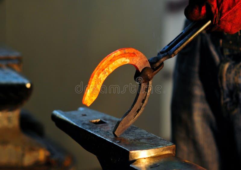 O ferreiro guarda uma ferradura quente crepitante imagens de stock