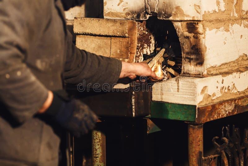 O ferreiro inflama um fogo na fornalha foto de stock