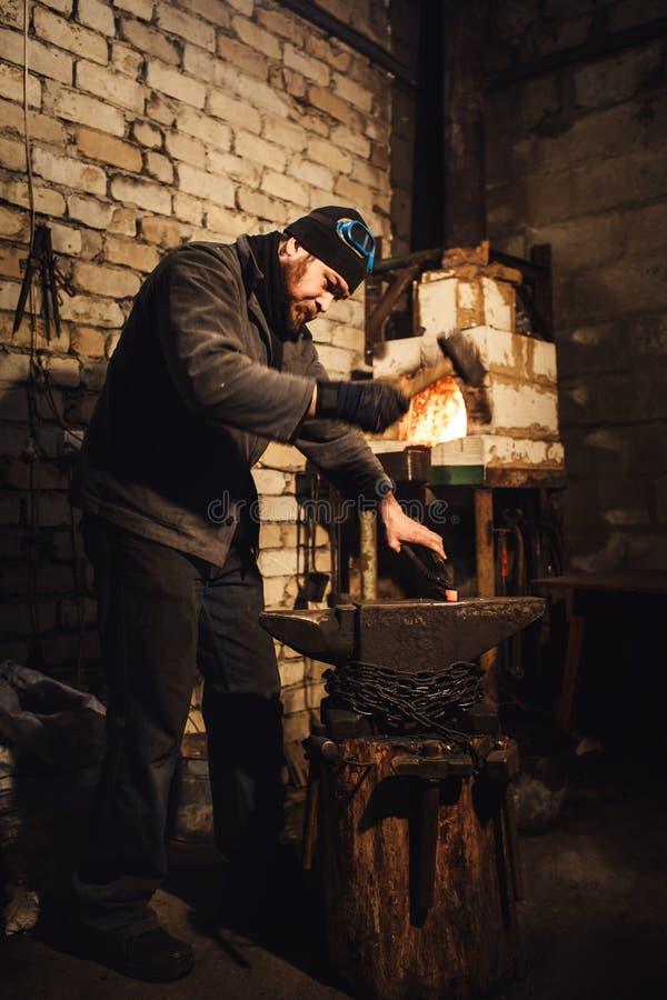 O ferreiro que forja manualmente o metal encarnado no batente foto de stock