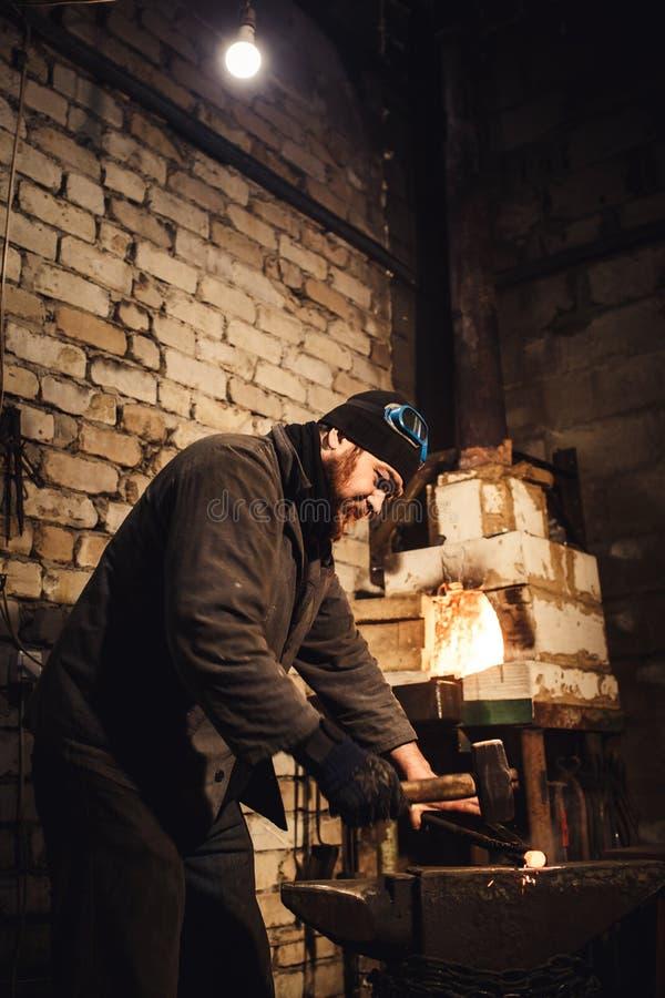 O ferreiro que forja manualmente o metal encarnado no batente e que voa faíscas imagens de stock