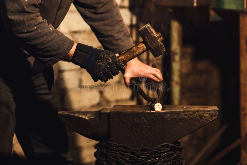 O ferreiro que forja manualmente o metal encarnado no batente na forja fotografia de stock royalty free