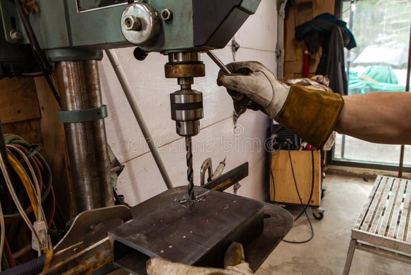 O ferreiro usa a imprensa de broca na garagem imagem de stock