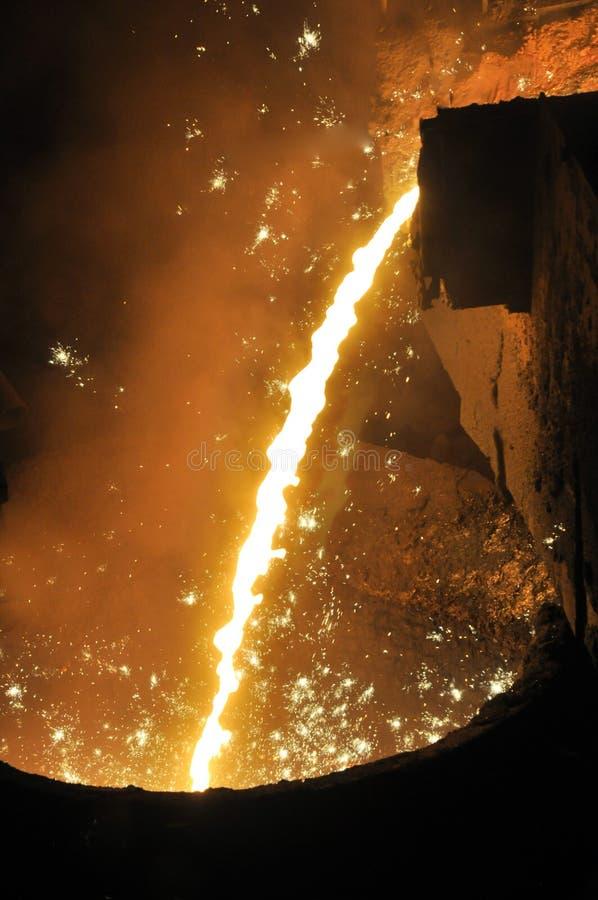 O ferro derretido flui na cubeta imagem de stock