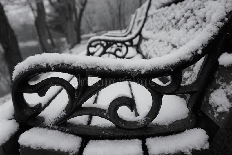 O ferro fundido enrola do braço do banco na neve imagem de stock