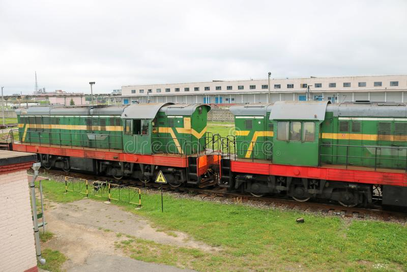 O ferro metálico verde rodou o trem de mercadorias, locomotiva para o transporte de bens nos trilhos na estação de trem imagem de stock royalty free