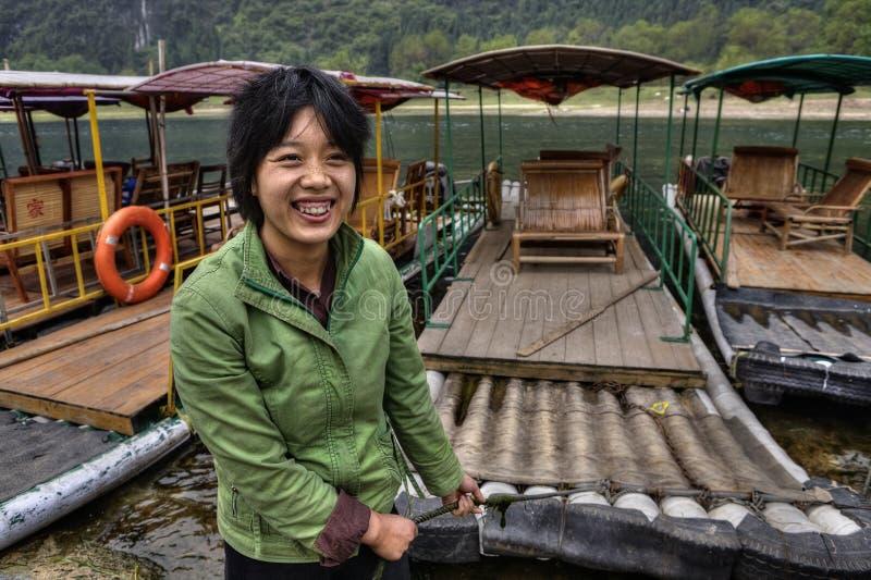 O ferryman asiático da menina amarra a jangada de bambu, e os sorrisos, Guangxi, China imagem de stock royalty free