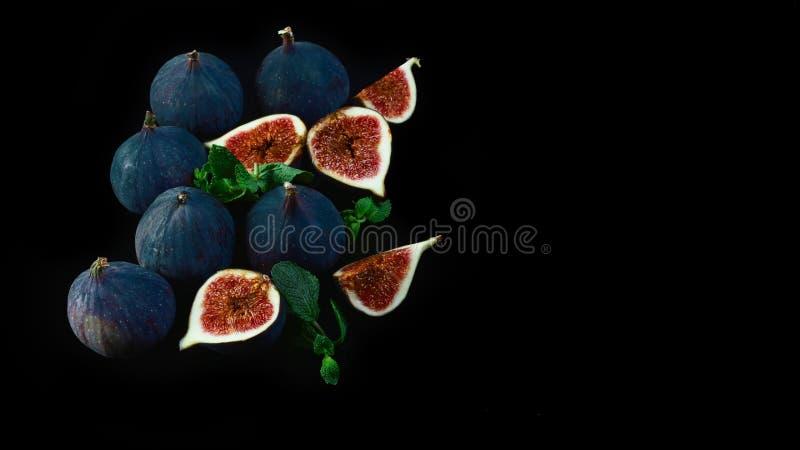 O figo roxo maduro frutifica, um cortado dentro parcialmente, isolado no fundo preto com reflexão Espaço da cópia da vista superi fotografia de stock royalty free