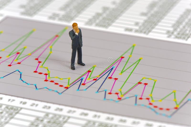 O figur modelo como o banqueiro está estando sobre a carta do mercado de valores de ação fotografia de stock royalty free