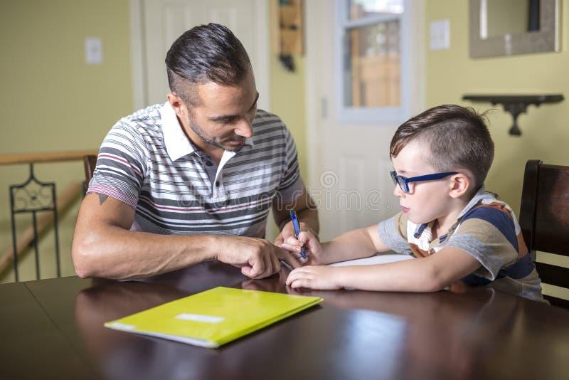 O filho de ajuda do pai faz trabalhos de casa O pai ajuda sua criança foto de stock