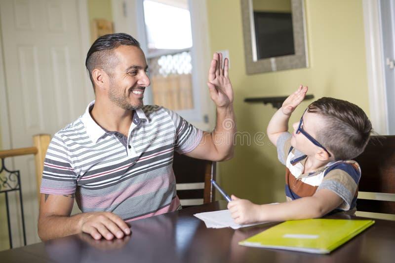 O filho de ajuda do pai faz trabalhos de casa O pai ajuda sua criança foto de stock royalty free