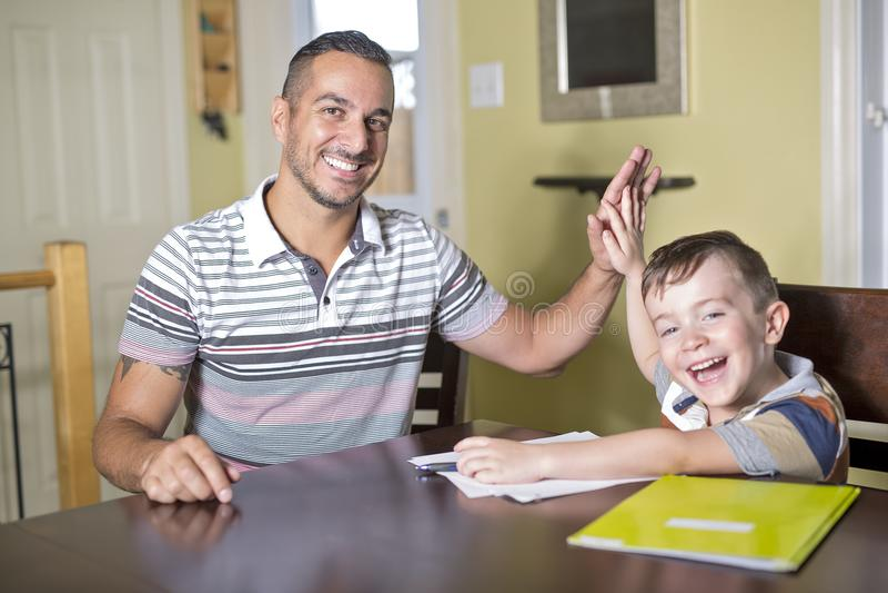 O filho de ajuda do pai faz trabalhos de casa O pai ajuda sua criança fotografia de stock