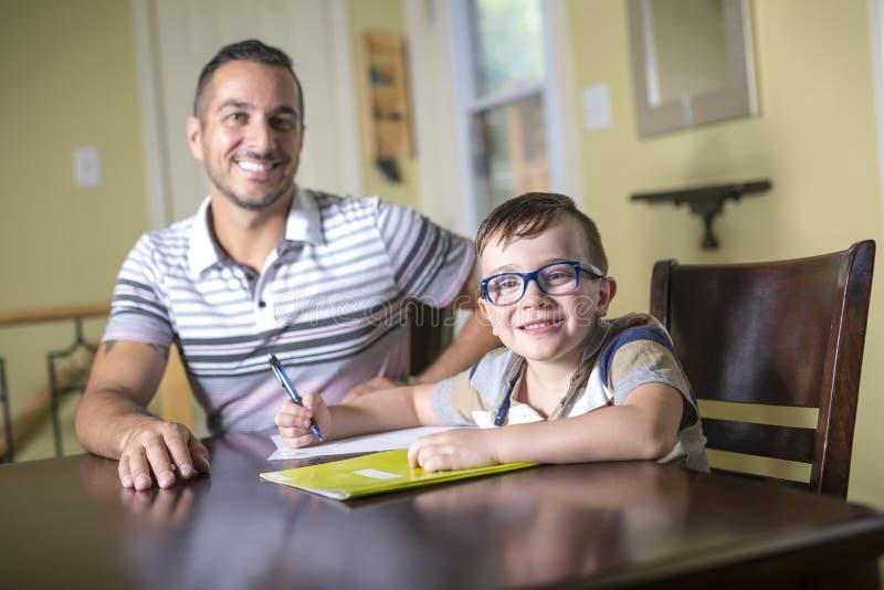 O filho de ajuda do pai faz trabalhos de casa O pai ajuda sua criança fotografia de stock royalty free
