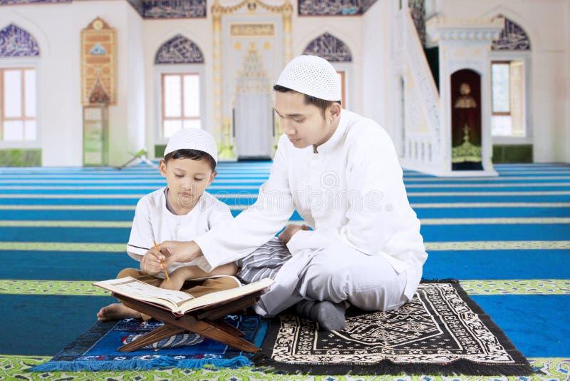 O filho de ensino do pai lê o Alcorão fotos de stock