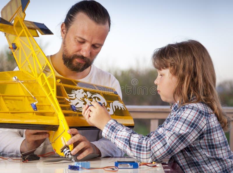O filho e o avião rádio-controlado caseiro feito pai dos aviões modelo são não direitos reservados feitos à mão foto de stock