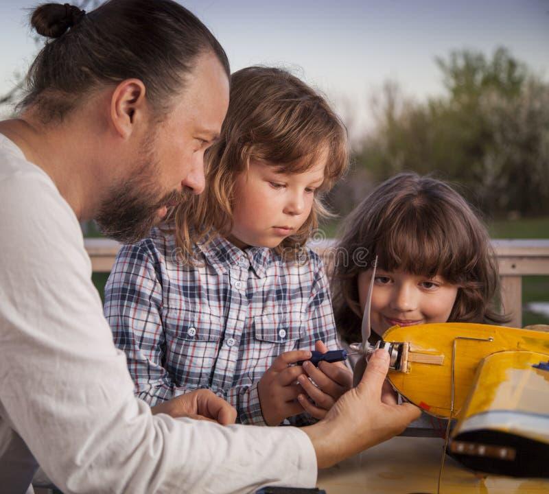 O filho e o avião rádio-controlado caseiro feito pai dos aviões modelo são não direitos reservados feitos à mão foto de stock royalty free