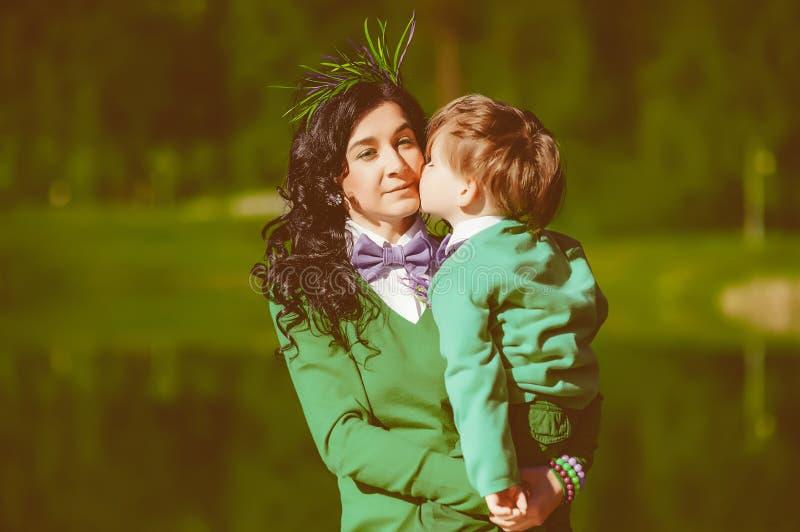 O filho está beijando sua mãe fotografia de stock