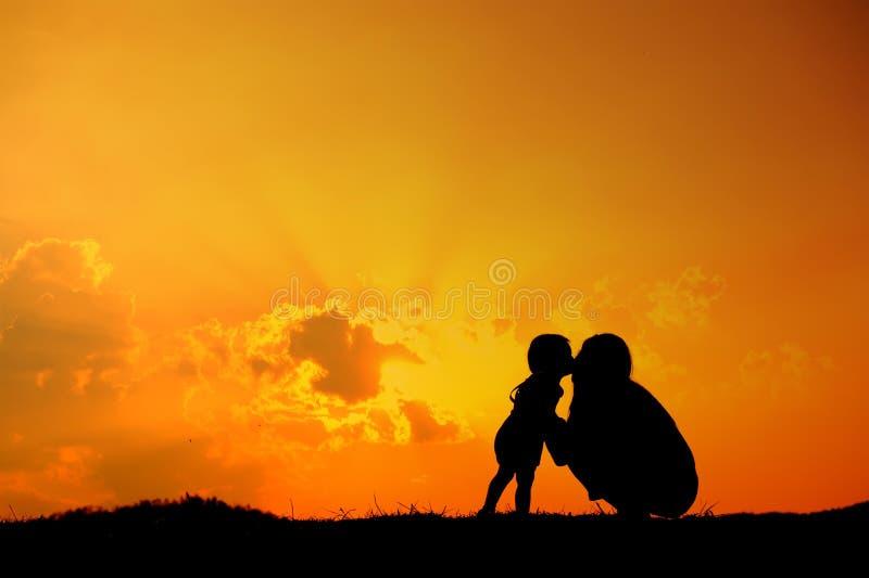 O filho está beijando sua mãe fora na silhueta do por do sol foto de stock