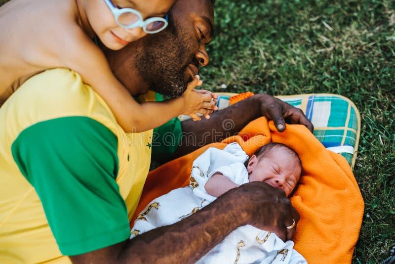 O filho está inclinando-se no ombro do paizinho de encontro que olha sua criança recém-nascida foto de stock royalty free