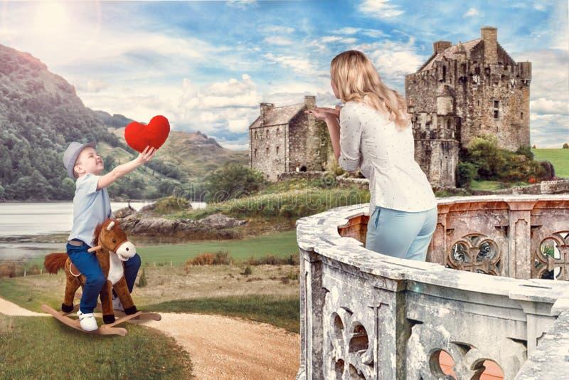 O filho no cavalo dá a um coração macio a mãe amado Príncipe pequeno a cavalo foto de stock
