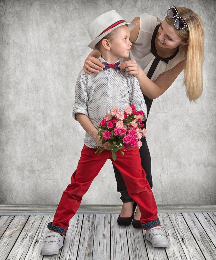 O filho pequeno dá a sua mãe amado um ramalhete bonito de rosas cor-de-rosa Mola, conceito das férias em família Dia do ` s das m fotografia de stock royalty free