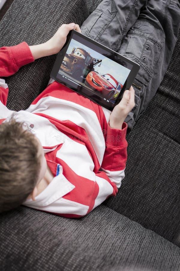 O filme das crianças de observação no iPad fotografia de stock royalty free