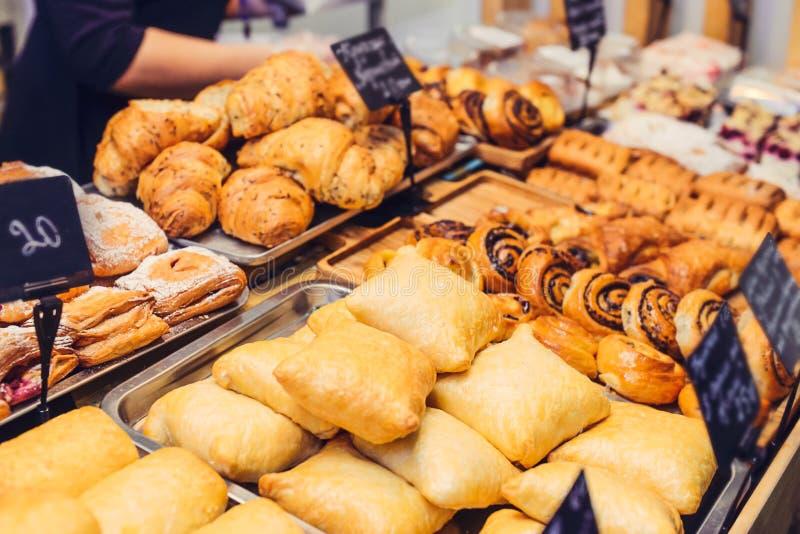 O fim acima cozeu recentemente bens da pastelaria na exposição na loja da padaria Foco seletivo imagens de stock