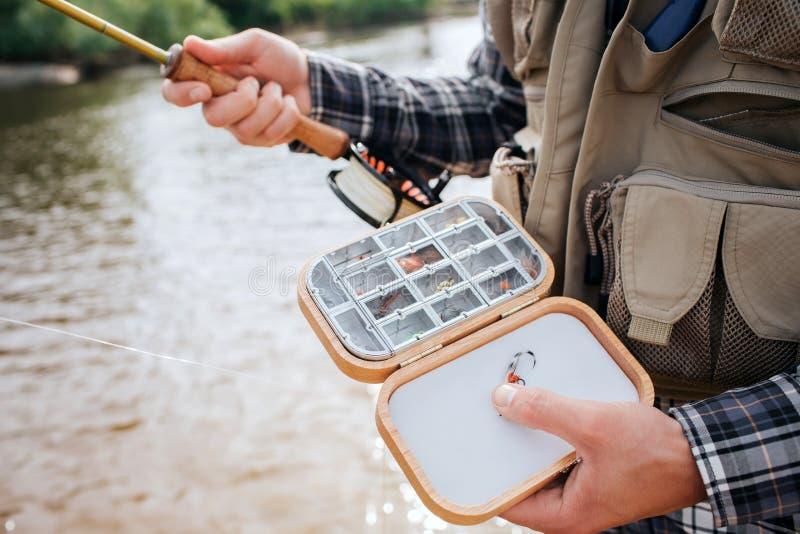 O fim acima da caixa de madeira com tipo diffeent da pesca artificial do silicone voa e iscas nele O homem guarda-o em uma mão imagem de stock